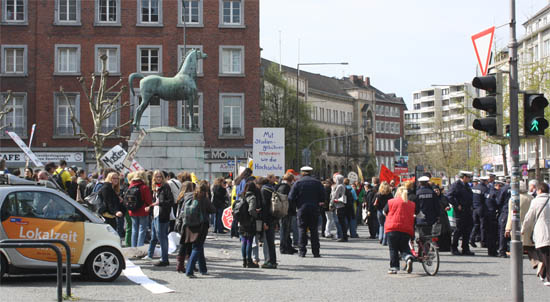 A group of people at Aachen's Theater place, as well as some police officers. Signs shown include messages against tuition fees.