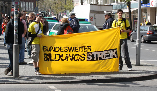 Two people with yellow T-shirts hold a banner with the Bildungsstreik logo.