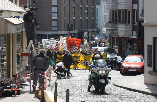 The demonstration, escorted by a police motorcycle and two police officers in front, ascends the hill towards Aachen's historic market place.